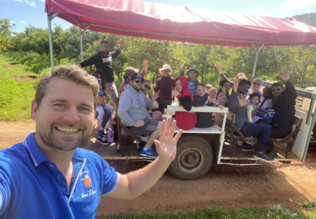 Adam-waving-with-tractor-tour-behind-him-Tractor-ride-and-fruit-picking-tour-The-Orchard-Perth